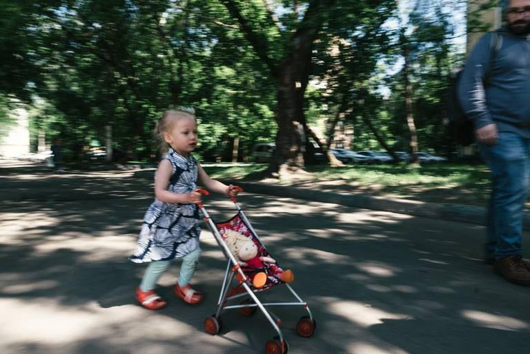 девочка бежит с коляской и куклой