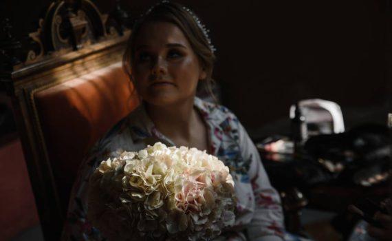 невеста с букетом в тёмной комнате