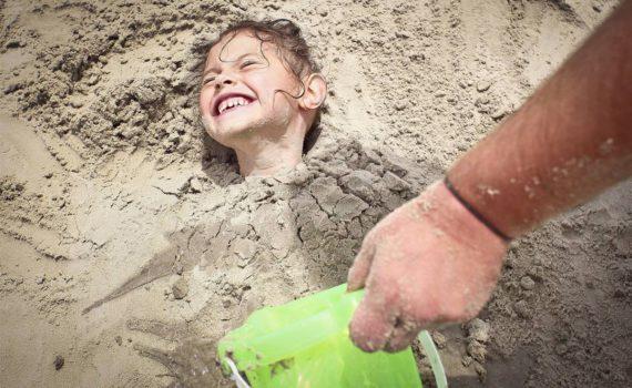 семейная фотсоессия на море девочка закопанная в песок