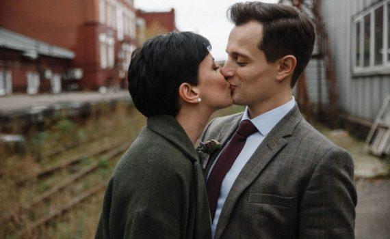 поцелуй красивой пары в пальто и пиджаке