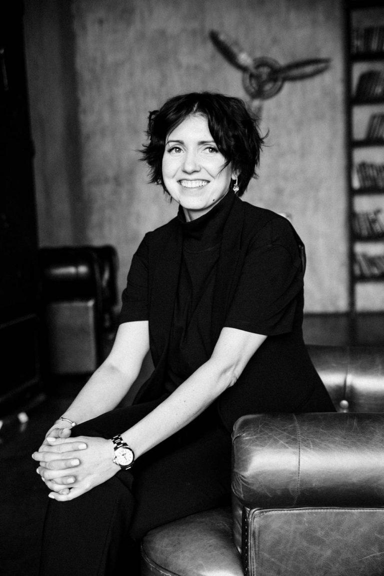 женский бизнес портрет в студии в кресле с улыбкой