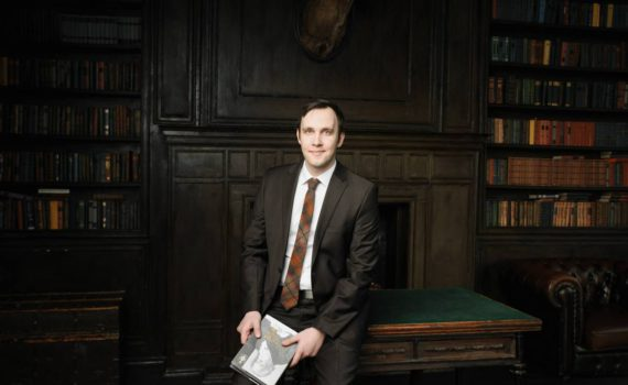 Мужской деловой бизнес портрет в пиджаке с книгой